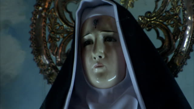 vídeos de stock, filmes e b-roll de a statue of a nun holds a cross and a skull. available in hd. - nun