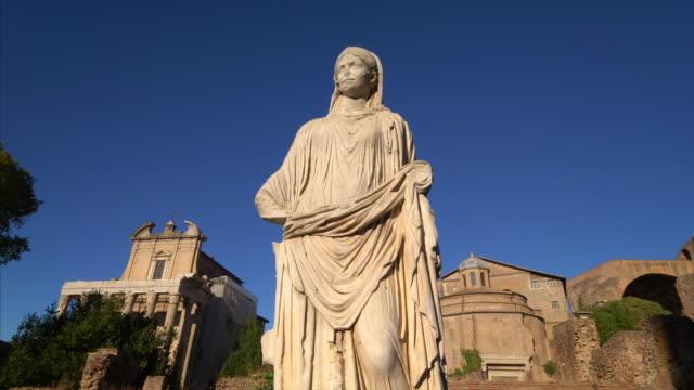 stockvideo's en b-roll-footage met statue of a woman with  the roman forum ruins in background in rome, italy - vrouwelijke gestalte