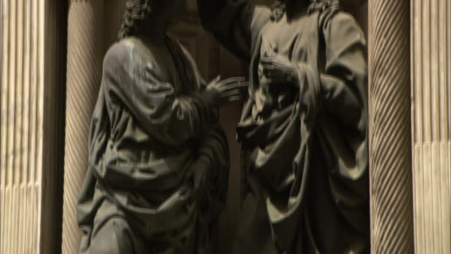 a statue of an apostle and jesus christ stands between two pillars. - apostle stock videos and b-roll footage