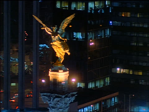 Statue of angel with office buildings in background at night /  Independence Monument, Mexico City, Mexico