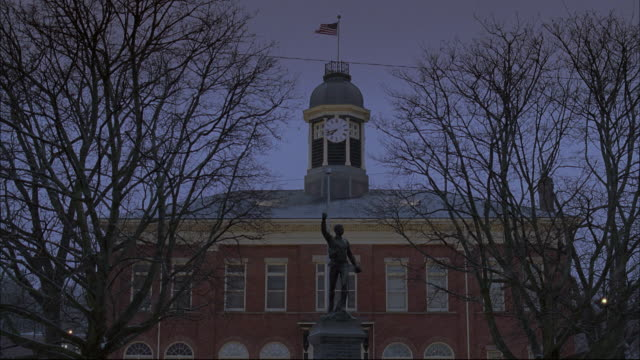 la statue of arthur t. h. williams in front of city hall with tower clock and flag waving / united states - rathaus stock-videos und b-roll-filmmaterial