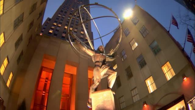 vídeos de stock e filmes b-roll de a statue of atlas stands in front of the rockefeller center in midtown manhattan. - estátua de atlas