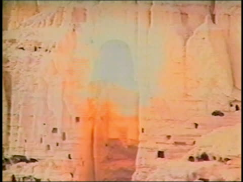 vídeos de stock e filmes b-roll de ms statue of bamiyan buddha exploding / cloud of dust / afghanistan asia / audio - buda