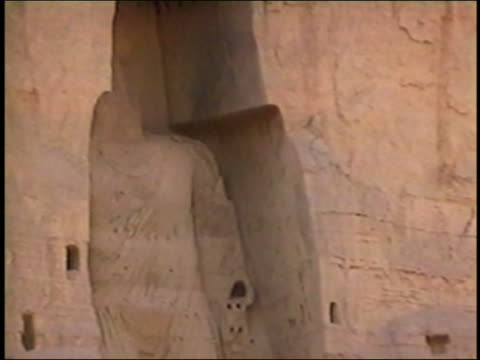 zi statue of bamiyan buddha exploding / zoom out smoke / afghanistan asia / audio - buddha stock-videos und b-roll-filmmaterial