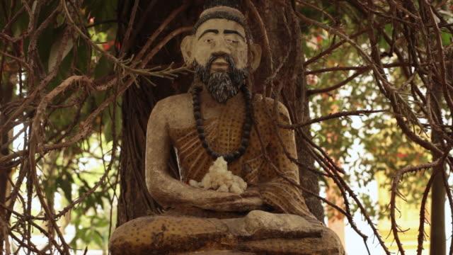 ms statue of bearded cross legged figure in front of tree / vientiane, laos - figura maschile video stock e b–roll