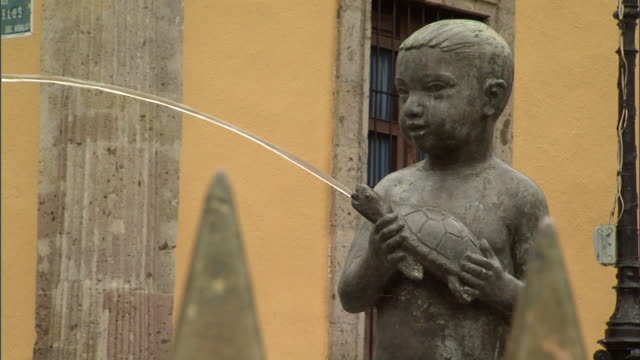hd ms statue of boy holding turtle turtle squirting water rack focus to top of tips of pointy metal fence jal mexico mx - squirting stock videos and b-roll footage
