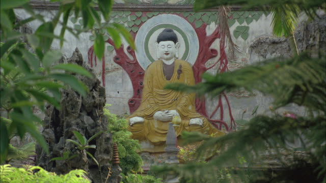 A statue of Buddha sits in a garden in Vietnam.
