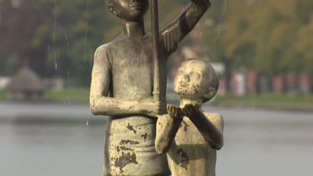 A statue of children sheltering under an umbrella stands by Lake Pfaffenteich MecklenburgVorpommern Germany NNBZ126J ABSA627D