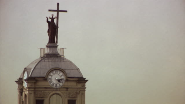 ms statue of christ and cross atop church clock tower / bogota, colombia - turmuhr stock-videos und b-roll-filmmaterial