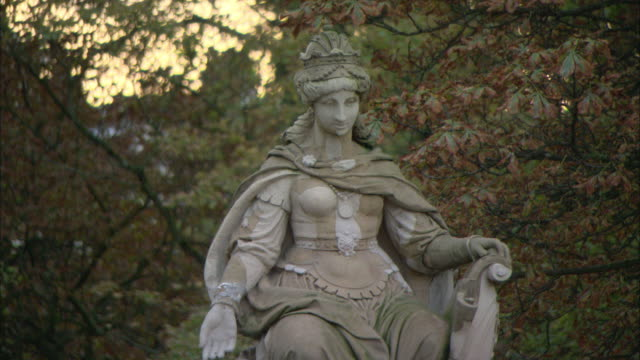 ms statue of crowned woman with, fall colored leaves in background / amsterdam, holland - female likeness stock videos & royalty-free footage