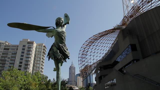 vídeos de stock, filmes e b-roll de ms td statue of dancing girl in front of melbourne art center / melbourne, victoria, australia - figura feminina