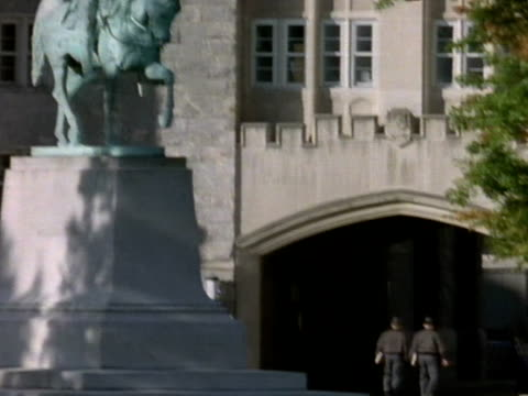 Statue of George Washington on horseback near school building TD cadets walking into archway of building at United States Military Academy