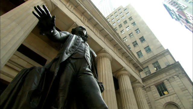 a statue of george washington stands in front of the federal hall national memorial in new york city. - statue stock videos & royalty-free footage