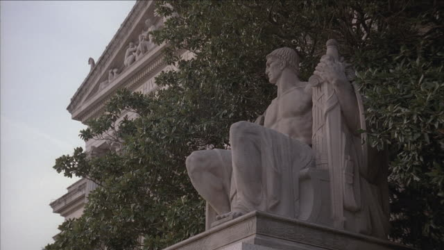 stockvideo's en b-roll-footage met la statue of heritage by james earl fraser and pediment of national archives building beyond / washington, d.c., united states - national archives washington dc