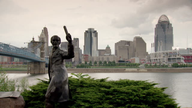 vídeos y material grabado en eventos de stock de statue of john a roebling and john a roebling suspension bridge and downtown cincinnati in background, ohio - río ohio
