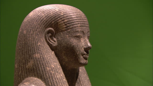 A statue of King Tut stands against a green wall in Luxor.