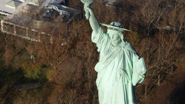 statue of liberty above autumnal trees on liberty island. shot in 2011. - artbeats stock videos & royalty-free footage