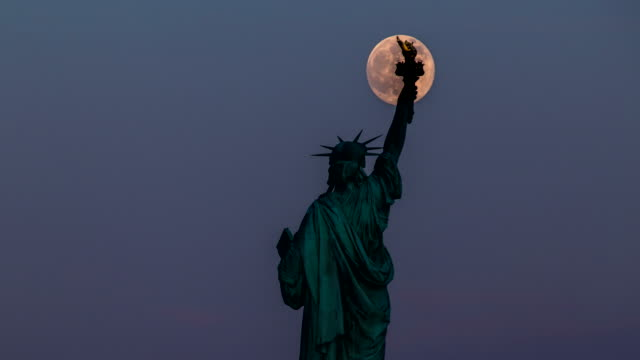 statue of liberty and full moon - 4k time lapse - satellite video stock e b–roll