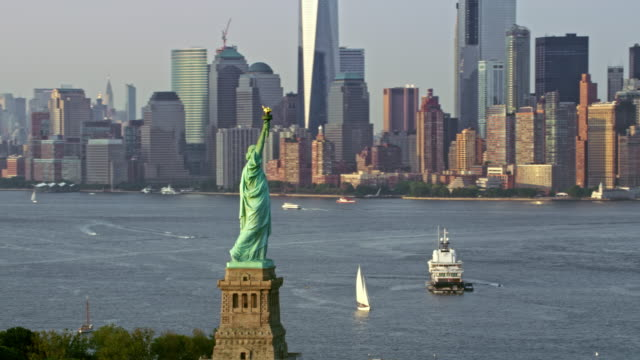 aerial statue of liberty and lower manhattan in sunshine - cultura americana video stock e b–roll
