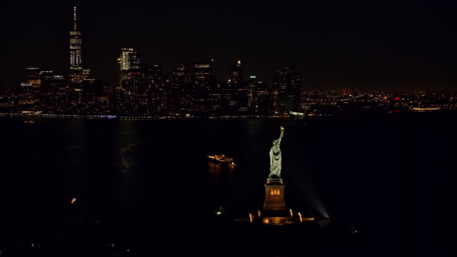 vídeos de stock e filmes b-roll de aerial statue of liberty and manhattan at night - estátua
