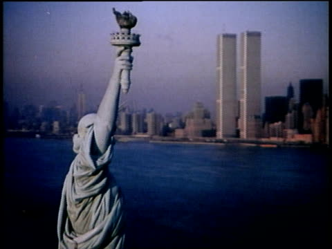 1976 aerial pan statue of liberty and world trade center towers in background / new york city - world trade centre manhattan stock videos and b-roll footage