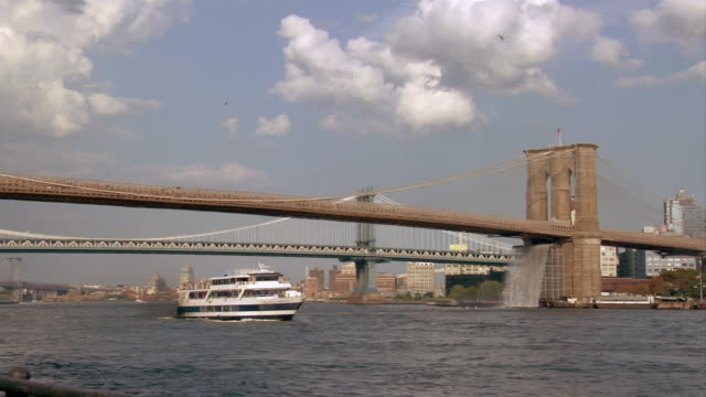 A Statue of Liberty ferry passes under the Brooklyn Bridge.
