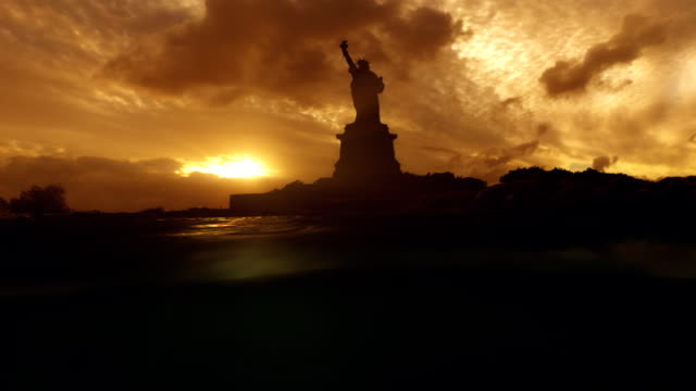 statue of liberty from water level sun sets behind it. - statue of liberty new york city stock videos & royalty-free footage