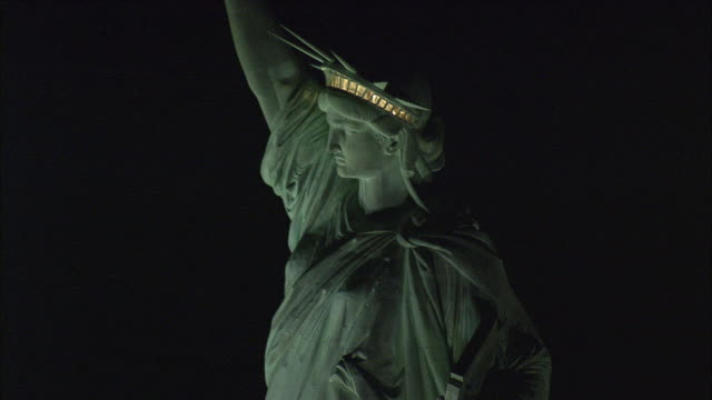 LOW AERIAL Statue of Liberty illuminated at night / New York City, New York, USA