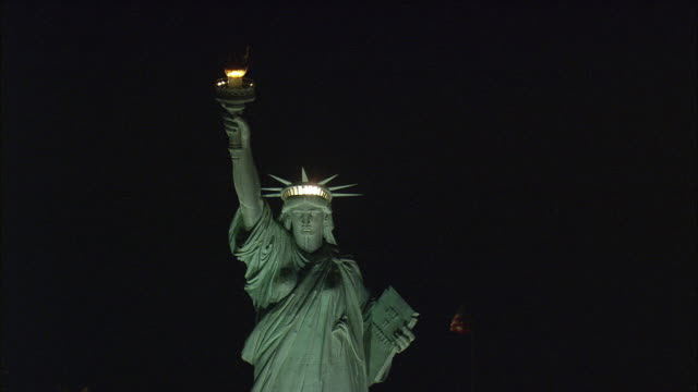 low aerial statue of liberty illuminated at night / new york city, new york, usa - female likeness stock videos & royalty-free footage