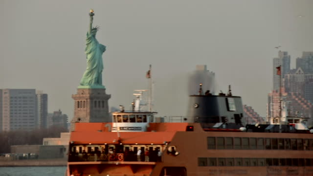 ms statue of liberty in manhattan and ferry is seen going past / new york, united states - ferry stock videos & royalty-free footage