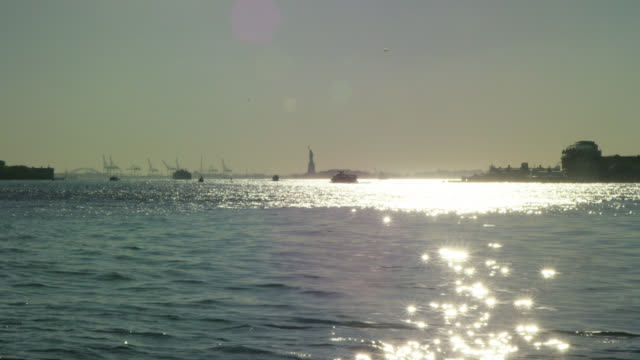 statue of liberty in the harbor with a boat at sunset wide angle - porto di new york video stock e b–roll