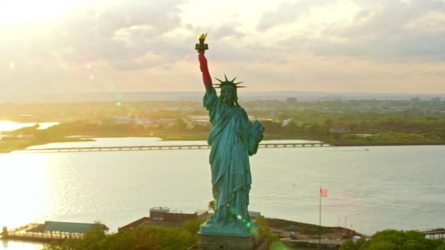 vídeos de stock e filmes b-roll de aerial statue of liberty on liberty island at sunset with nyc in the background - estátua