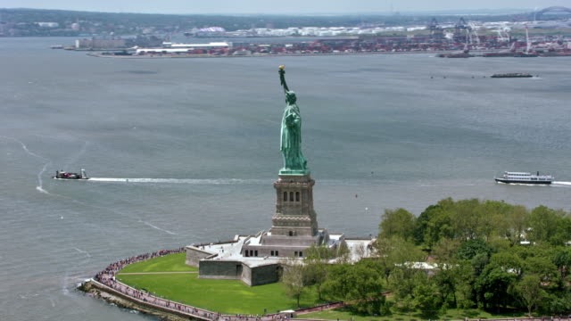 aerial statue of liberty on liberty island in sunshine - statue of liberty new york city stock videos & royalty-free footage