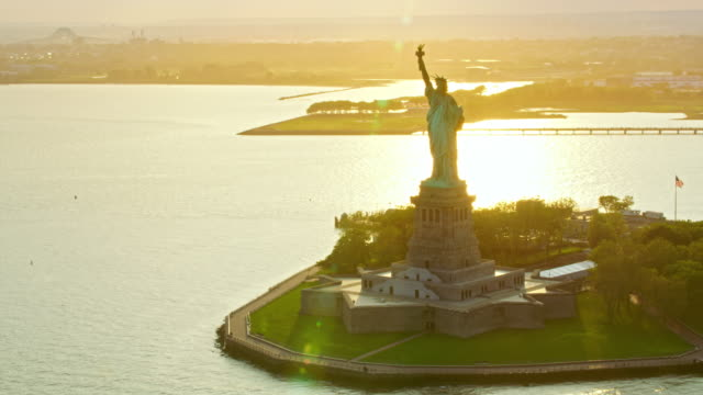 aerial statue of liberty on liberty island shining in setting sun - flaming torch stock videos & royalty-free footage