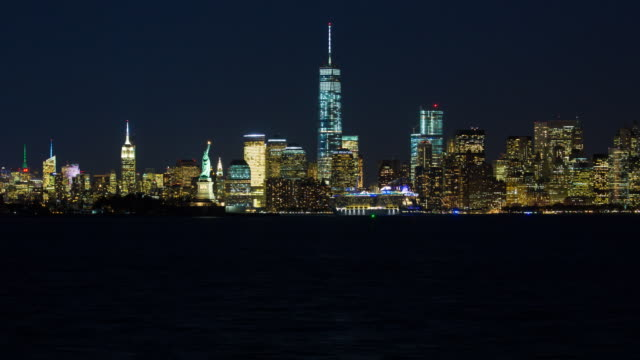 Statue of Liberty, One World Trade Center and Downtown Manhattan across the Hudson River, New York, Manhattan, United States of America - Time lapse