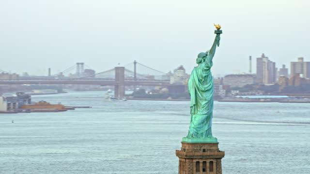 vídeos de stock e filmes b-roll de aerial statue of liberty overlooking new york - statue of liberty new york city