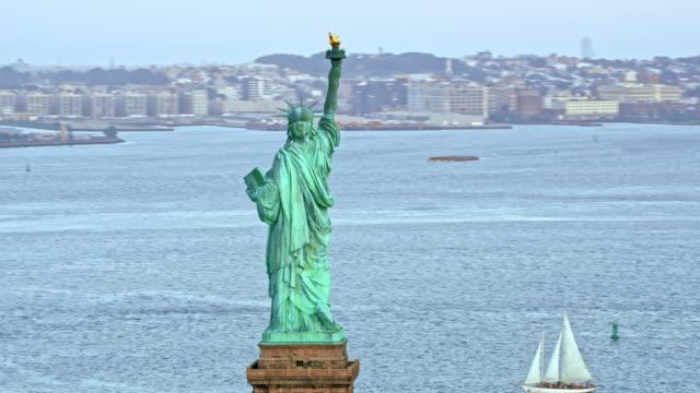 vídeos de stock, filmes e b-roll de aérea estátua da liberdade, erguendo-se acima das águas do porto de nova york - estátua