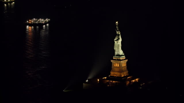 aerial statue of liberty shining in new york harbor at night - statuetta video stock e b–roll