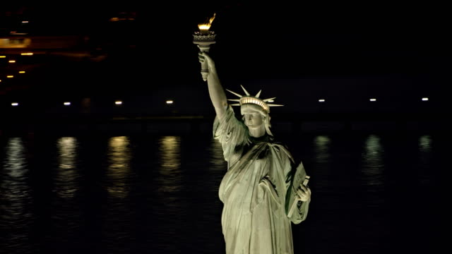 vídeos de stock e filmes b-roll de aerial statue of liberty shining in the harbor at night - statue of liberty new york city