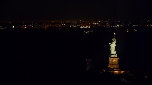 vídeos de stock e filmes b-roll de aerial statue of liberty shining in the new york harbor at night - statue of liberty new york city