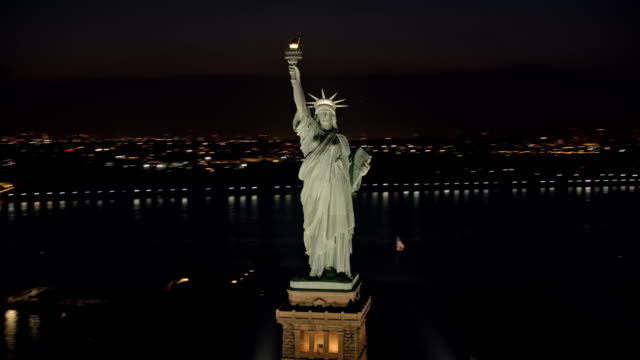 aerial statue of liberty shining in the night with lower manhattan seen in the background - statue of liberty new york city stock videos & royalty-free footage