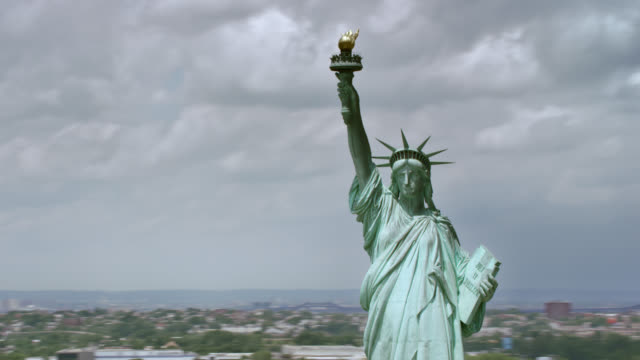 aerial statue of liberty with governors island and manhattan - statue of liberty new york city stock videos & royalty-free footage