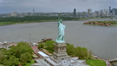 aerial statue of liberty with liberty island on a sunny day - statue of liberty new york city stock videos & royalty-free footage