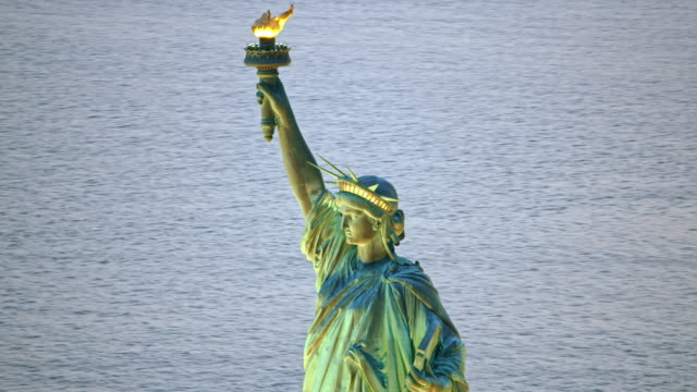 aerial statue of liberty with lit torch in the evening - statue of liberty new york city stock videos & royalty-free footage
