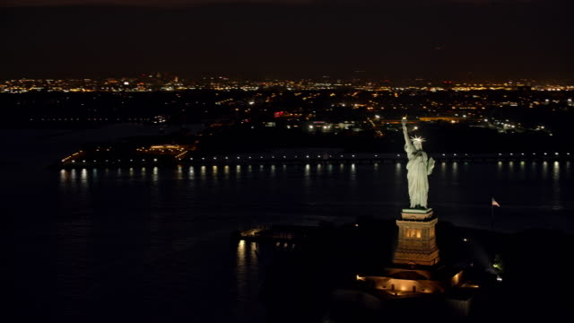 vídeos de stock e filmes b-roll de aerial statue of liberty with new york in the background at night - statue of liberty new york city