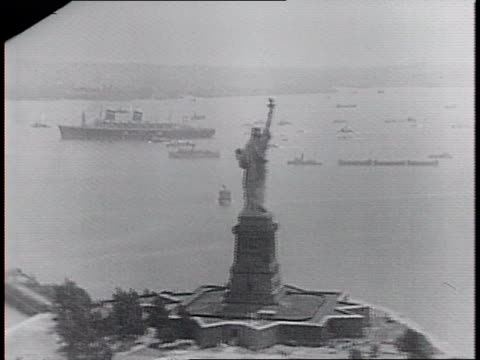 statue of liberty with ss america passing by in the distance / ship and tugboats / ship, tugboats and new york city skyline in background. - porto di new york video stock e b–roll