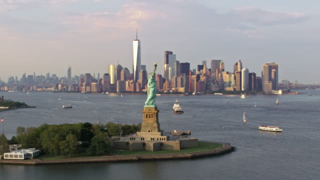 aerial statue of liberty mit der freedom tower im hintergrund - new york stock-videos und b-roll-filmmaterial