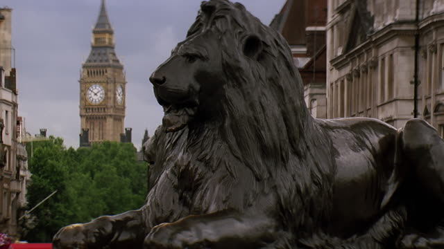 cu statue of lion with bus and big ben in background / london, united kingdom - sculpture stock videos & royalty-free footage