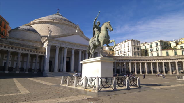 Statue of man on horseback in front of  San Francesco di Paola cathedral at Piazza del Plebiscito in Naples, Italy