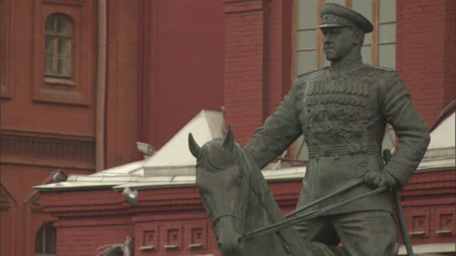 a statue of marshal zhukov towers in moscow's red square. - red square stock videos & royalty-free footage